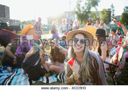 Portrait smiling young woman drinking with friends at summer music festival campsite - Stock Photo