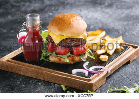 Homemade traditional hamburger with beef, tomato, cheese, aragula, served on wooden slate serving board with french fries and ketchup sauce on dark te - Stock Photo