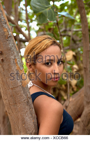 A beautiful young woman leaning against a tree - Stock Photo