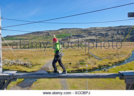 Mature man balancing on wooden plank on high rope course - Stock Photo