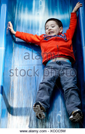 Boy sliding down slide in playground - Stock Photo