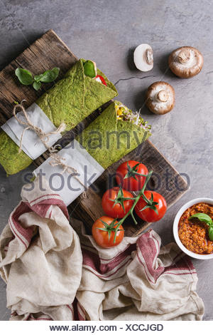 Green spinach matcha tortillas wrapped in paper with ingredients above. Sweet corn, avocado, green paprika, sprouts, mushrooms served on wood board ov - Stock Photo