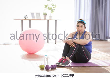 Young fat woman tired sitting down during exercise - Stock Photo