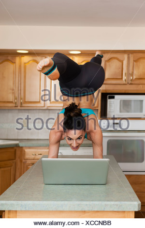 A woman doing a handstand balancing on a kitchen top and checking her laptop. - Stock Photo