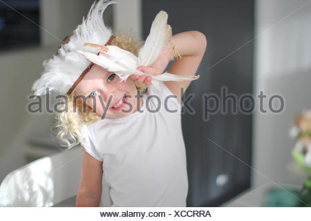Portrait of girl wearing feather headdress holding feathers - Stock Photo