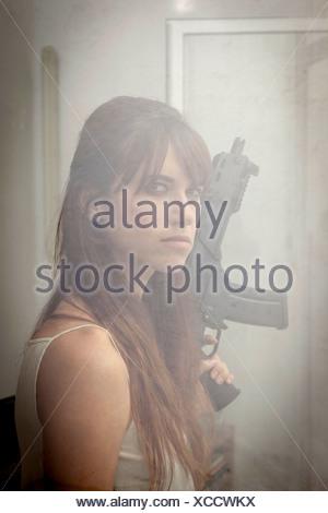 Woman holding machine gun at window - Stock Photo