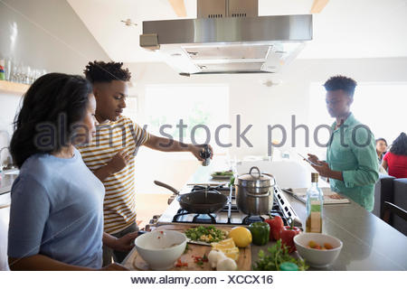 African American mother and teenage sons cooking in kitchen - Stock Photo