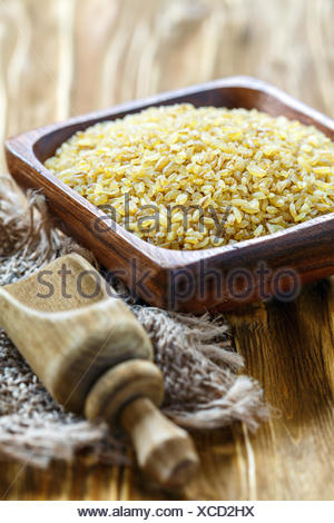 Uncooked bulgur in wooden bowl and scoop. - Stock Photo