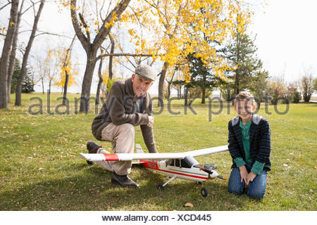 Portrait grandfather and grandson with model airplane in autumn park - Stock Photo