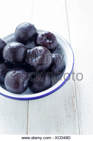Plums - Whole in a Bowl,on a white rustic background - Stock Photo