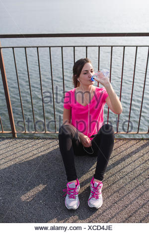 Sportive young woman drinking water after running at lakeshore - Stock Photo