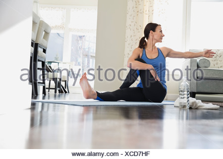 Mature woman doing yoga on mat - Stock Photo