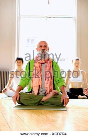 Mature man in lotus pose in yoga class - Stock Photo
