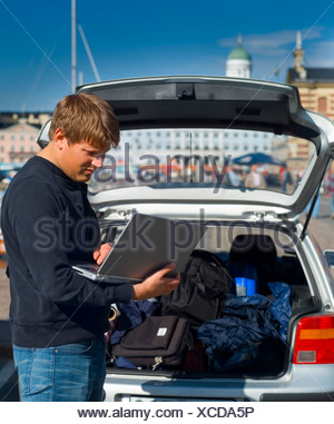 Young man using laptop in front of an open luggage trunk in car - Stock Photo