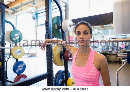 Portrait confident woman at barbell in gym - Stock Photo
