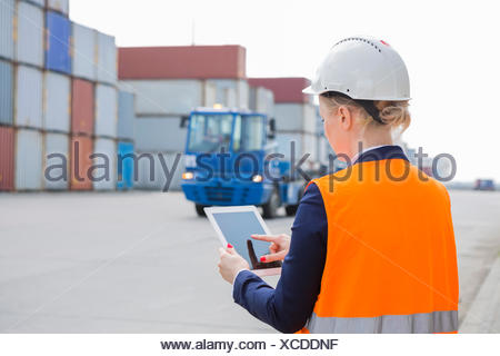 Rear view of female engineer using tablet PC in shipping yard - Stock Photo