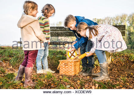 Children looking into picnic basket - Stock Photo