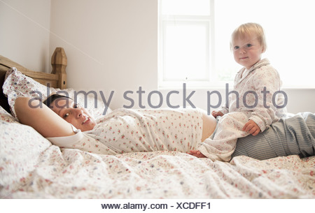 Toddler girl sitting with mother in bed - Stock Photo