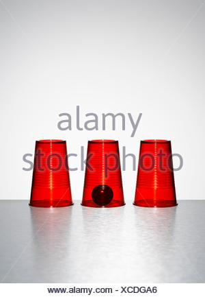 Ball under middle of three clear red cups - Stock Photo