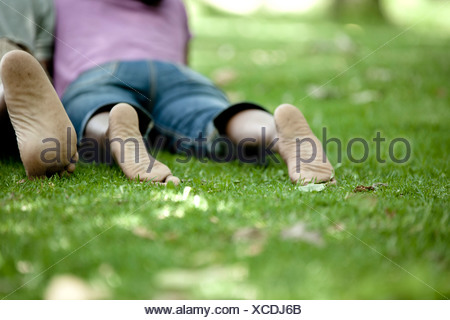 Shot from behind of a young black couple lying on the grass in a park - Stock Photo