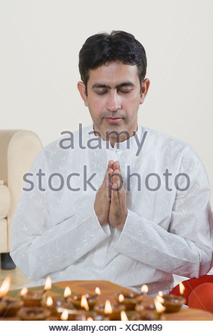 Close-up of a mid adult man praying with oil lamps in front of him - Stock Photo