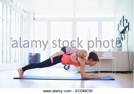 Mid adult mother practicing yoga with toddler daughter on top of her - Stock Photo