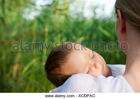 Over shoulder portrait of mid adult mother and sleeping baby daughter in garden - Stock Photo