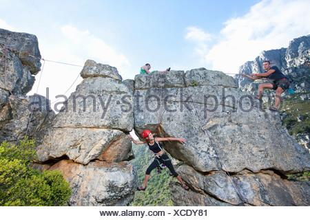 Three rock climbers climbing up rock formation - Stock Photo