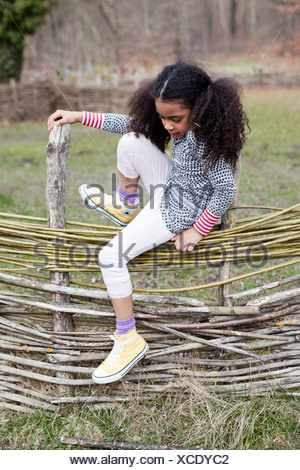 young girl climbing over fence - Stock Photo