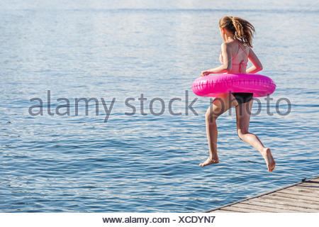 Girl jumping off a dock by Balsam Lake wearing inflatable ring; Ontario, Canada - Stock Photo