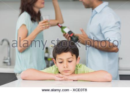 Closeup of a sad son while parents quarreling - Stock Photo