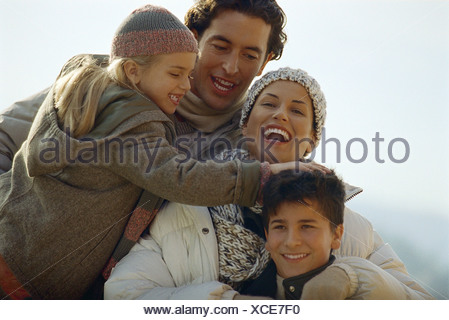 Family laughing together outdoors, daughter ruffling her brother's hair - Stock Photo