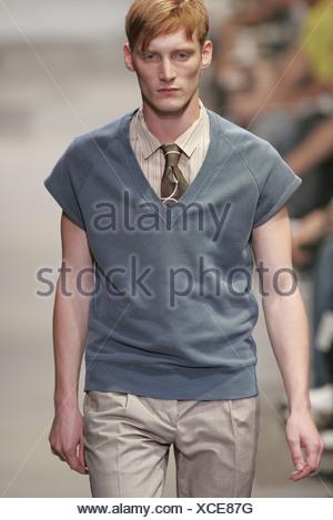 8dd26fb3009fb ... Prada Milan Menswear S S Male wearing grey v neck tank top over biege  shirt Blurred spectators