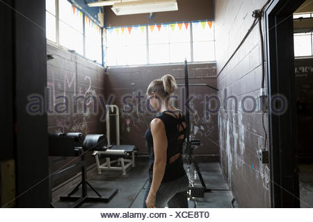 Fit woman weightlifting in gritty gym - Stock Photo