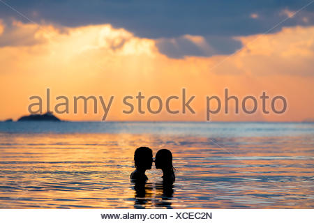 Couple kissing, silhouettes at sunset - Stock Photo