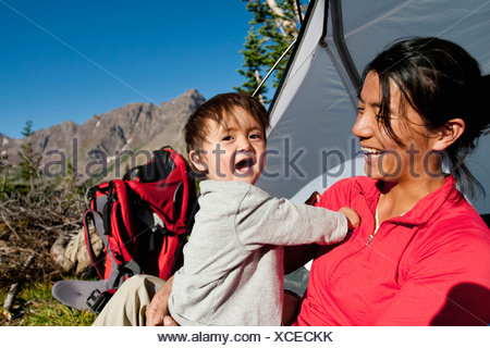 Mother watches 14 month old son play in meadow at camp. Backpacking trip Maroon Bells in Snowmass Wilderness outside Aspen - Stock Photo