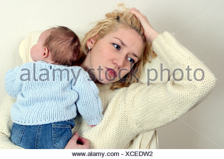 PND Tired mom holding newborn baby in arms. She is likely suffering from Postnatal depression. - Stock Photo