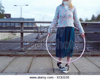 Woman with hula hoop on motorway bridge - Stock Photo
