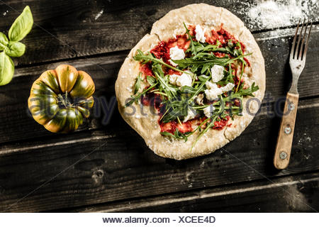 Pizza on dark wooden table, tomato, basil, fork, South Tyrol, Italy - Stock Photo
