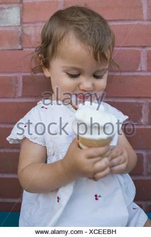 Baby girl enjoying soft serve ice cream cone - Stock Photo
