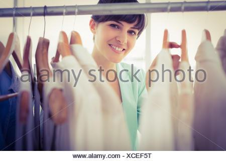 Pretty girl looking trough the wardrobe - Stock Photo