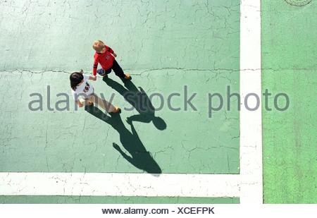 Hi angle of brother and sister walking - Stock Photo