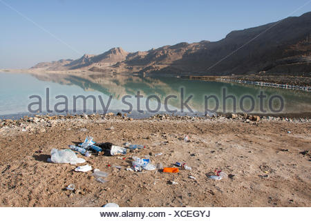 Dirty Beach. Rubbish left by visiters on the shore of the Dead Sea, Israel - Stock Photo