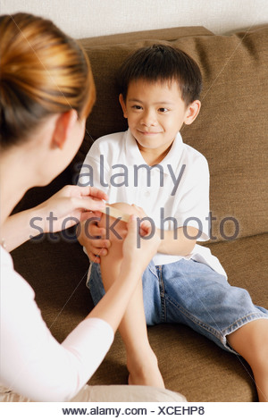 Mother putting bandage on son's knee - Stock Photo