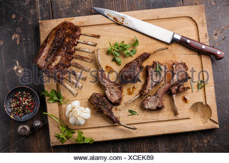 Roasted lamb ribs and kitchen knife on wooden cutting board on dark background - Stock Photo