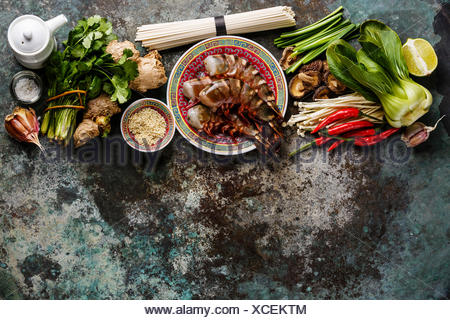 Ingredients for cooking Asian food with Tiger shrimps, udon noodles, mushrooms, greens, vegetables, spices on metal background copy space - Stock Photo
