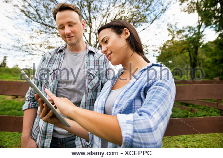 An organic farm in the Catskills. Two people looking at the screen of a digital tablet. - Stock Photo