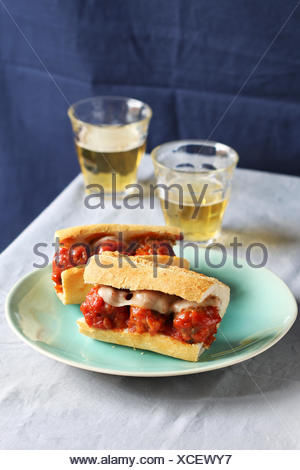 Two meatball sandwiches on a plate with two glasses of fresh beer - Stock Photo