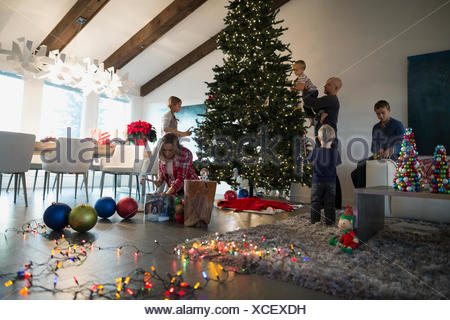 Family decorating Christmas tree in living room - Stock Photo