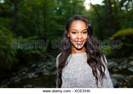 Portrait of happy young woman in darkened forest - Stock Photo